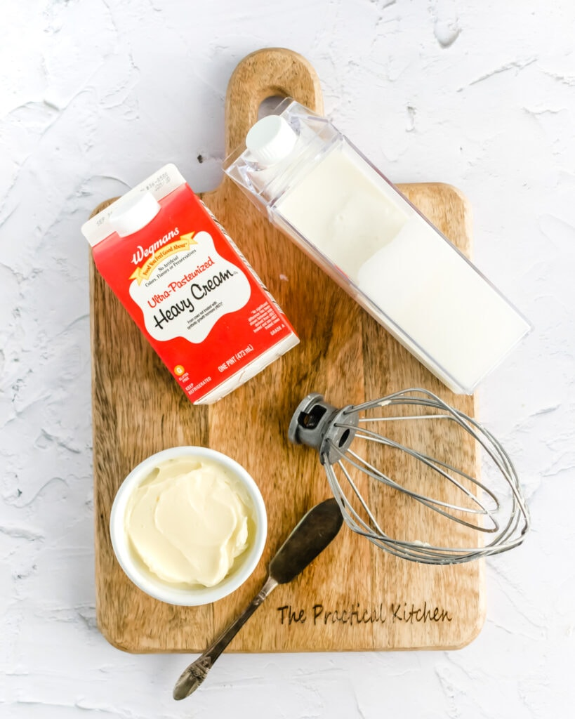 an overhead shot of heavy cream, butter, buttermilk, and a wire whisk on a wooden cutting board