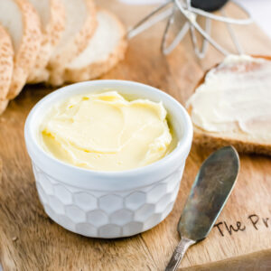 a small white ramekin of homemade butter on a wooden board with a butter knife and slices of bread