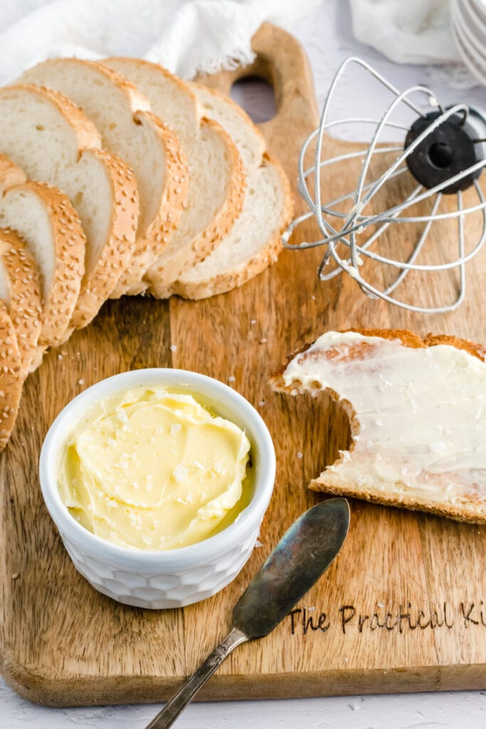 a small white ramekin with butter in it sits on a wooden board with slices of bread and a wire stand mixer whisk