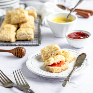 a plate of mini honey butter biscuits with jam sits in front of a cooling rack with other mini biscuits and bowls of honey butter and jam