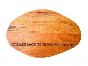 an oval shaped wooden cheeseboard with an engraving that reads: PACK YOUR KNIVES AND GO