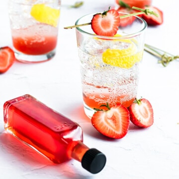 a small bottle of strawberry syrup lies next to a strawberry soda with lemon and strawberry garnish\