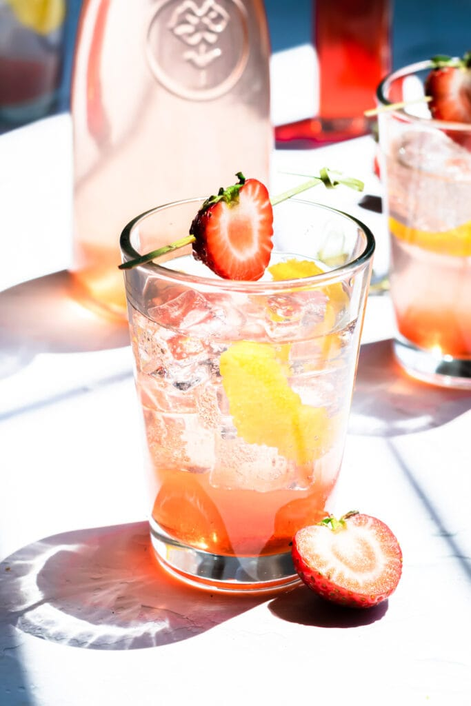 a glass of strawberry soda in front of a carafe of strawberry soda