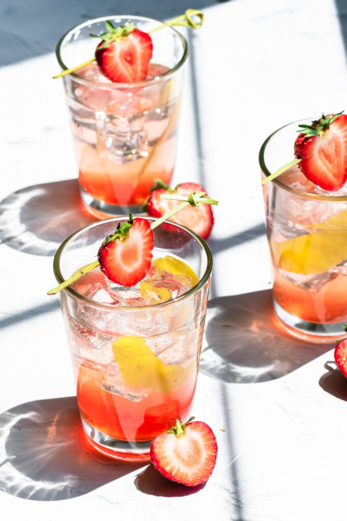 three glasses of strawberry soda with ice garnished with strawberry halves and lemon peel