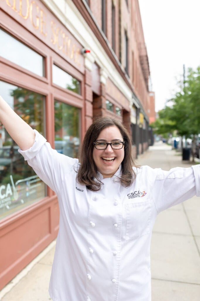 rebecca wearing her white chef coat outside of her culinary school with her hands in the air looking happy