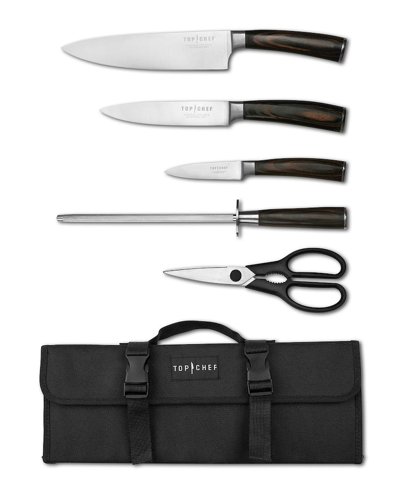 two chefs knives, a paring knife, a honing steel, and pair of kitchen shears with curved dark wooden handles and a black knife carrying case