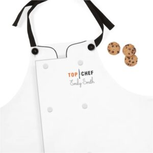a white apron with a fake chef coat front on it and black strap. the left breast has the top chef logo and a custom name written in script.