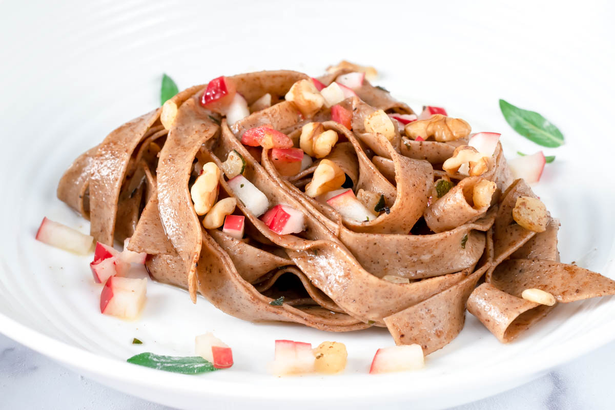 pasta in a bowl with apples and walnuts